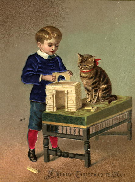 circa 1885: A Christmas greetings card showing a boy playing with building bricks, and a cat looking on. (Photo by Hulton Archive/Getty Images)
